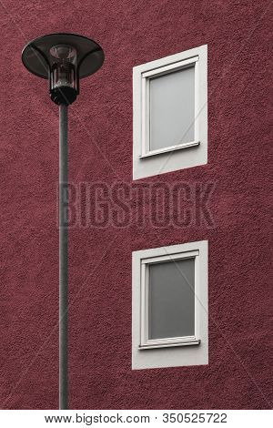 Streetlamp In Front Of A Dark Red Residential Building With White Windows.