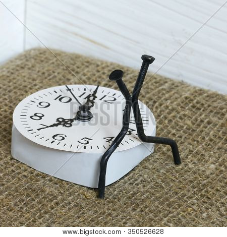 Figurines Of Man Made From Carpentry Nails. Sit On The Watch Dial Back To Back. Symbol Of The Inexor