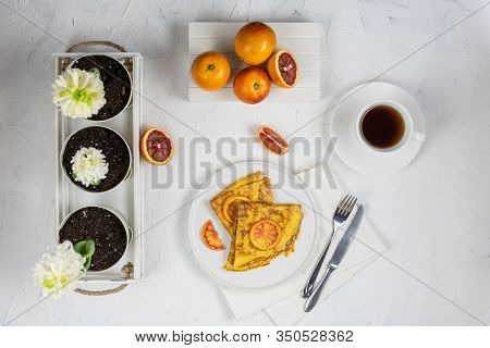Flat Lay Of The Spring Breakfast For One Person. On The White Table Are Plate With A Crepe Suzette,
