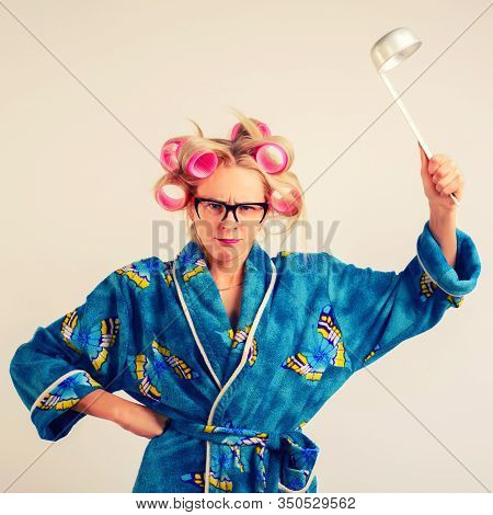 A Harsh Woman In A Dressing-gown And Curlers Swings A Ladle.