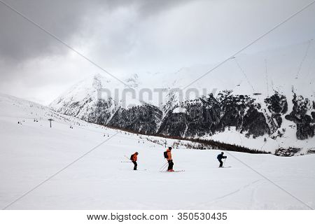 Off-piste Snowy Ski Slope With Skiers In High Mountains And Cloudy Sky At Winter Grey Day. Ski Area