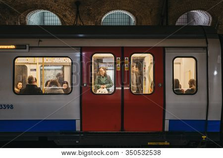 London, Uk - November 26, 2019: London Underground Train On A Station Platform, People Seen Though T