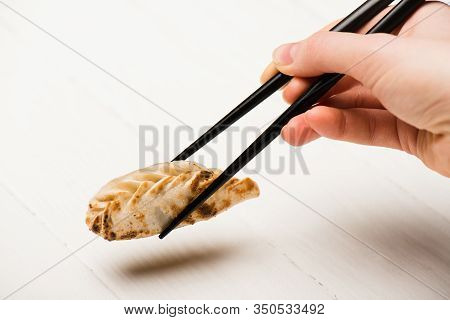 Cropped View Of Woman Eating Delicious Gyoza With Chopsticks At White Wooden Table
