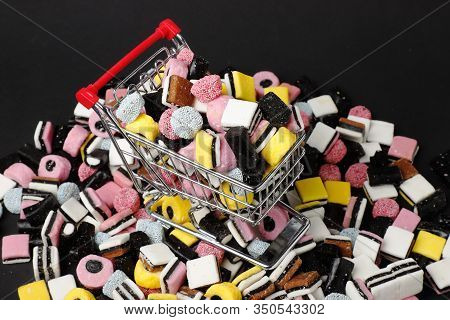 Miniature Shopping Cart Filled And Surronded With English Liquorice Candy.