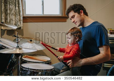 Father Teaching Baby Boy To Play Drums. Parent With Toddler Child Having Fun And Spending Time Toget