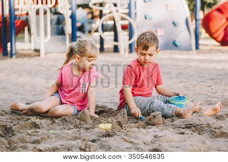 Two Caucasian Children Sitting In Sandbox Playing With Beach Toys. Little Girl And Boy Friends Havin