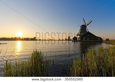Windmills By A River At Suset