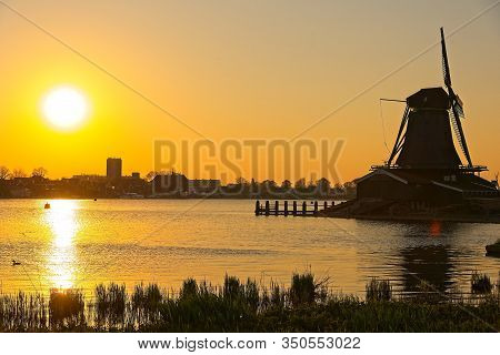 Windmill By A River At Suset