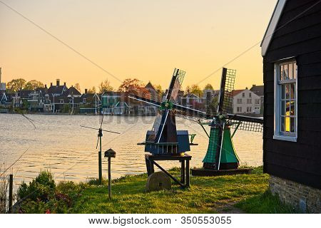 Miniature Windmills By A River At Suset
