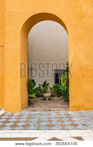 SEVILLE, SPAIN - December 09 2019: Arch leading through a colorful orange wall to enclosed courtyard garden with green plants and small water feature in Real Alcazar, Seville, Spain