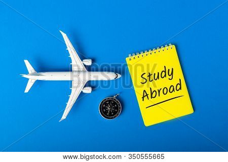 Study Abroad - Message On Blue Background With Airplane Model. Learning A Language And Studying Abro