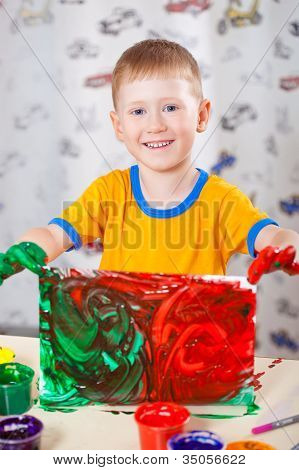 little boy holding painted picture