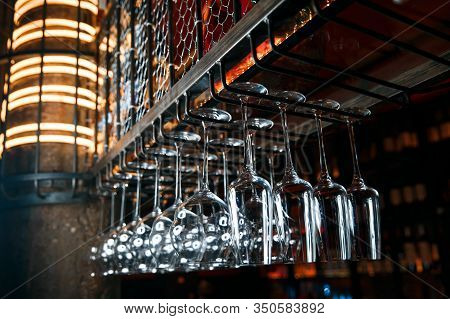 Clean Glasses Over The Bar. Clean Glasses For Alcoholic Beverages Hang In Several Rows Over The Bar