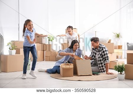 Happy Family Unpacking Moving Boxes At Their New Home