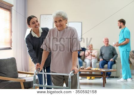 Care Worker Helping To Elderly Woman With Walker In Geriatric Hospice