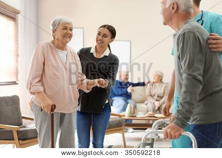 Care Workers Helping To Elderly Patients To Walk In Geriatric Hospice
