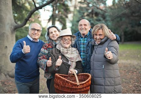 group of seniors in the park with thumbs raised