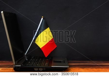 Flag Of Belgium , Computer, Laptop On Table And Dark Background