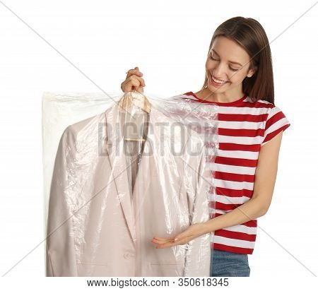 Young Woman Holding Hanger With Jacket In Plastic Bag On White Background. Dry-cleaning Service