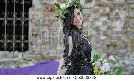 Woman In The Spring. A Wreath Of Meadow Grass And Flowers Is Worn On The Brunettes Head. White Peoni