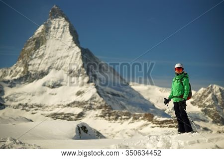 Young Woman Skier Standing On Snow On Backgroung Of Matterhorn Mountain And Bright Blue Sky, Freerid