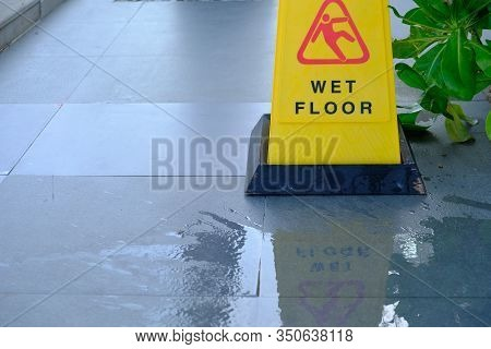 Close Up Of Warning Caution At Outdoor Walkway. Yellow Sign Showing Warning Of Caution Wet Floor Con