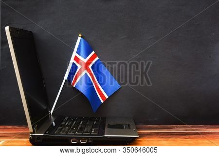 Flag Of Iceland , Computer, Laptop On Table And Dark Background