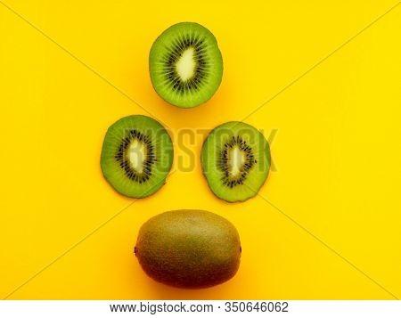 Three Circles Of Kiwi And One Whole Kiwi On A Yellow Background. Kiwi Cutaway