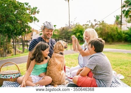 Happy Family With Their Dog In A Good Summer Day. The Family Playing With Dog. Happy Family Doing Pi