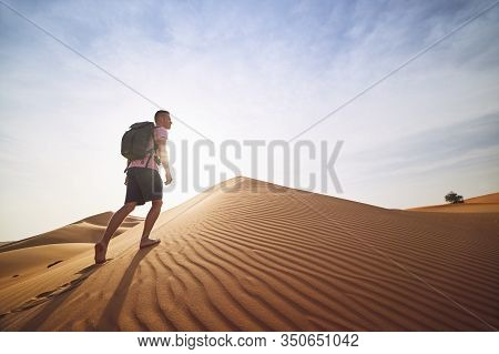Desert Adventure. Young Man With Backpack Walking On Sand Dune. Abu Dhabi, United Arab Emirates