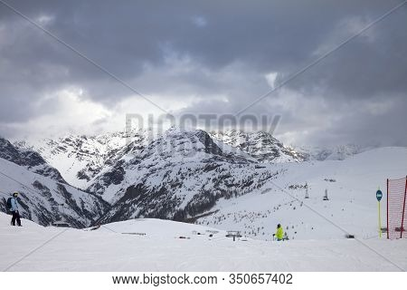 Snowy Ski Slope With Skier And Snowboarder In High Mountains And Cloudy Sunlit Sky At Winter Gray Da