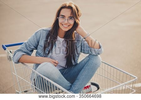 Optimistic Modern Indian Female In Casual Outfit Smiling And Looking At Camera While Sitting Crossed