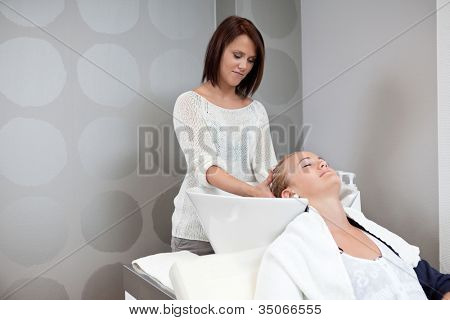 Relaxed young woman receiving head massage at hair salon