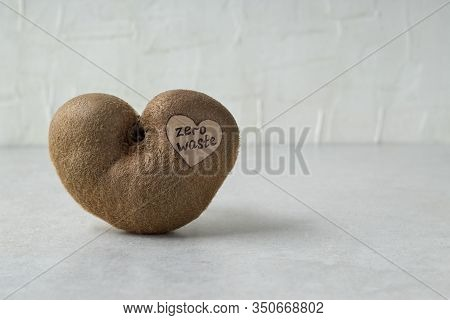 Ugly Heart Shaped Kiwi Fruit With Zero Waste Label On Grey Table, Space For Text. Organic Misshapen