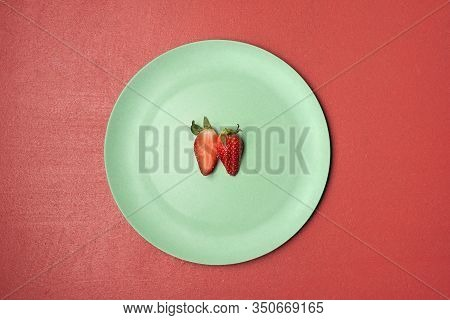 Organic Strawberry Cut In Half On Green Plate And Red Background. Above View Of Two Halves Of Strawb