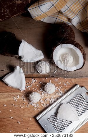 Close Up Of Coconut With White Pulp, Grater With Coconut Chip And White Candies On Wooden Background