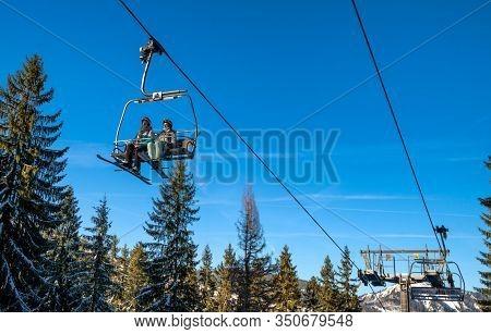 Demanovska Dolina, Slovakia - February 8: Skiers Sitting On Ski Lift Chair In Resort Jasna In Low Ta