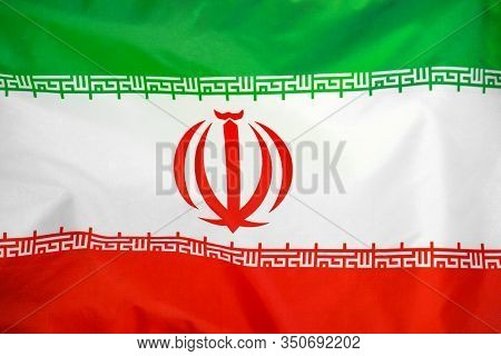 Fabric Texture Flag Of Iran. Flag Of Iran Waving In The Wind. Iran Flag Is Depicted On A Sports Clot