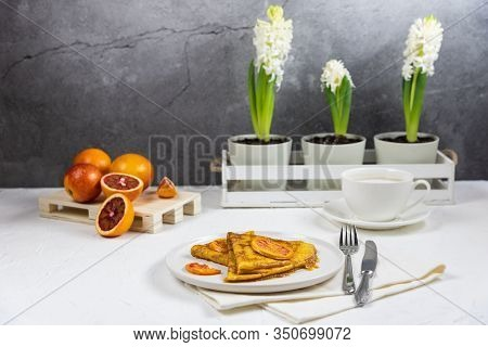 Spring Serving Breakfast For One Person. On The White Table Are Plate With A Crepe Suzette, Cup Of C