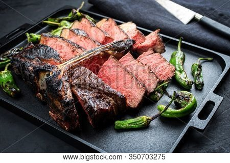 Barbecue dry aged wagyu porterhouse beef steak sliced with large fillet piece with hot chili as closeup on a modern design black cast iron tray