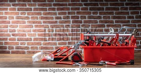 Toolbox With Different Worktools Against Brick Wall