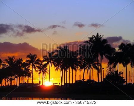 Sunsets Through Coconut Trees Over With Light Reflecting On Lagoon And Illuminating The Sky Orange O