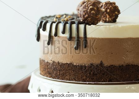 Mousse Cake Three Chocolate In Hand Of Woman. A Piece Of A Mousse Cake
