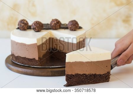"Mousse Cake Three Chocolate. A Piece Of A Mousse Cake ""three Chocolate""  Sprinkled With Grated Choco"