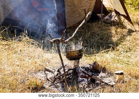 Camping Outdoors - Tents, Equipment And Cooking. Cooking At A Camping Site In Nature. The Bowler Is