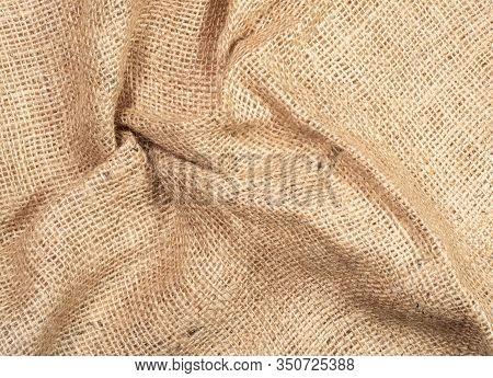 Brown Burlap Textile, Close Up View. Crumpled Burlap Fabric, Abstract Background. Texture Of Burlap