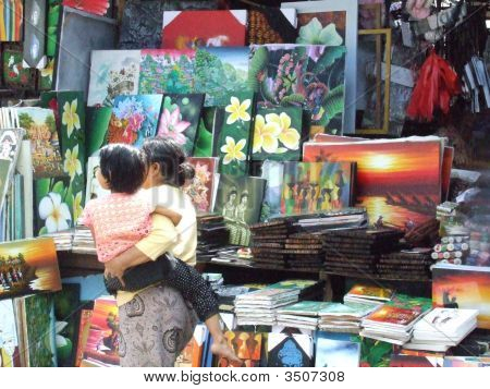 A Woman And Child Pass Paintings For Sale In Ubud, Bali, Indonesia
