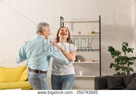 Happy Senior Couple Dancing In Living Room