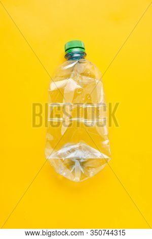 Used Plastic Bottle Of Water With Caps On Yellow Background. Recycling Concept