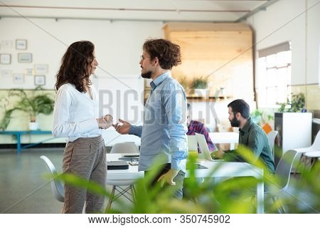 Side View Of Serious Man Talking With Confident Colleague. Two Coworkers Communicating In Open Space